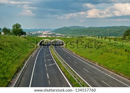 Empty asphalt highway with eco-duct for the Animals, the distant city of Carlsbad, storm clouds in parallel with the prospect of road - stock photo