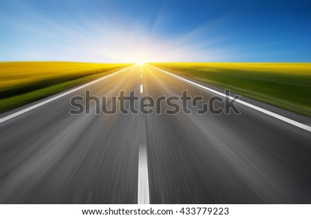empty asphalt road and floral field of yellow flowers with blur in motion. abstract nature background