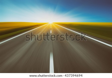 empty asphalt road and floral field of yellow flowers with blur in motion. abstract nature background. vintage picture - stock photo