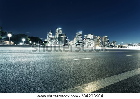 Empty asphalt road and illuminated modern cityscape background at night - stock photo
