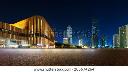Empty asphalt road and modern skyline at night - stock photo