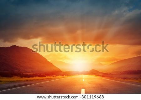Empty asphalt road and sun rising at skyline - stock photo