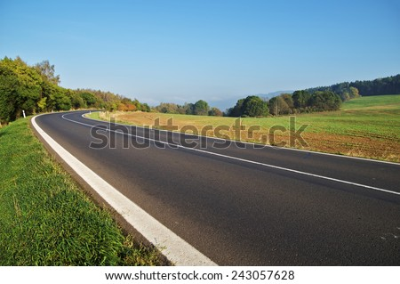 Empty asphalt road in countryside, bend of road, field in the background, forest on the horizon - stock photo