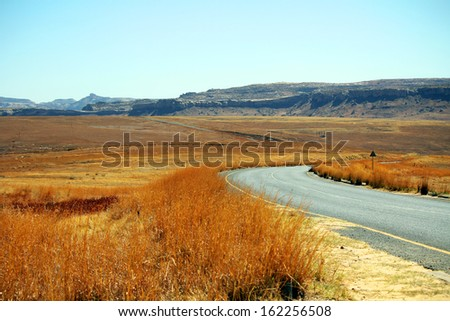 Empty asphalt road in Golden Gate Highlands National Park, South Africa - stock photo
