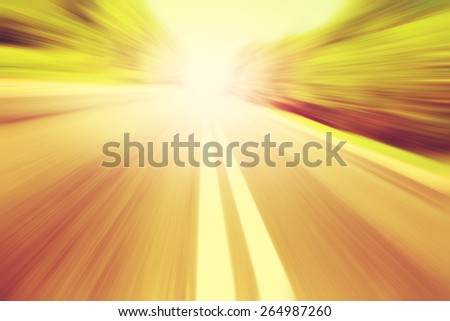 Empty asphalt road in motion blur at sunset. - stock photo