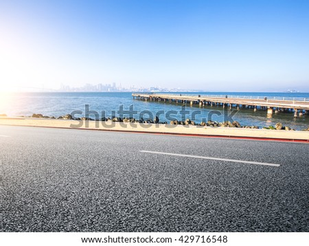 empty asphalt road near pier on sea with cityscape and skyline of san francisco in blue sky