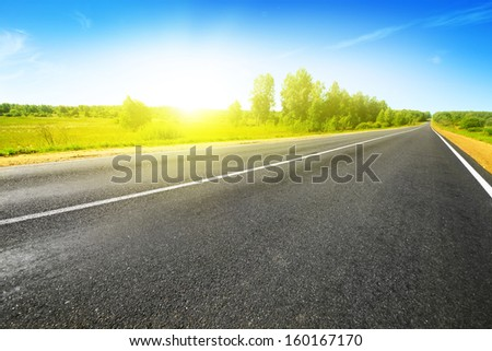 Empty asphalt road on bright summer day. - stock photo