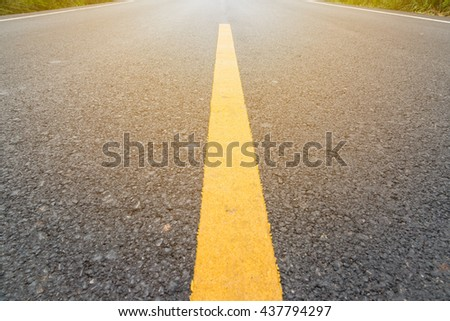 Empty asphalt road through the agricultural fields with yellow line towards