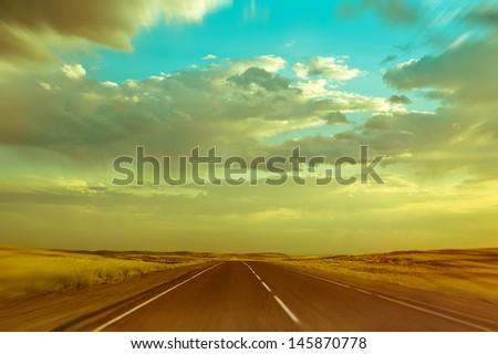 Empty asphalt road under dramatic sunset  cloudy sky in Kazakhstan. Motion blurred image, vintage style processing - stock photo
