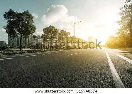 empty asphalt road with trees under sunshine - stock photo