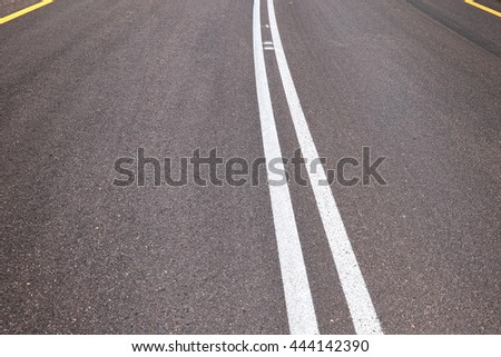 Empty asphalt two-way traffic road with a double solid white line and side restrictive yellow line. Road markings. Abstract background  - stock photo
