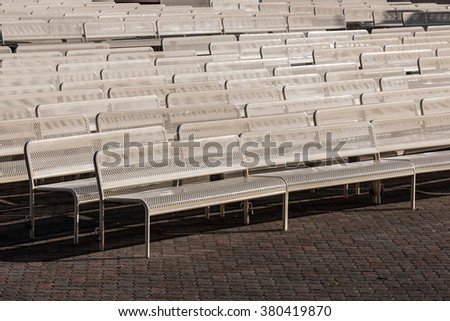 Empty audience benches in rows outdoors and facing right. - stock photo