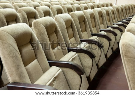 Empty auditorium with beige chairs, theatre or conference hall