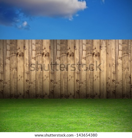 empty backdrop for your design - backyard with green lawn and wooden fence under a beautiful sky - stock photo