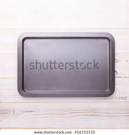 Empty baking tray on white wooden desk close up top view square