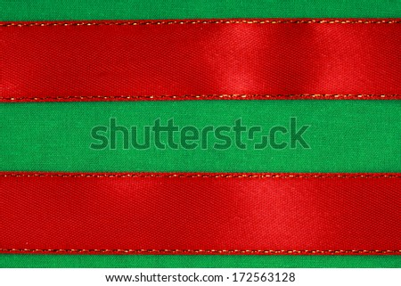 Empty banner on textile background. Red ribbon on green fabric cloth texture with copy space. - stock photo