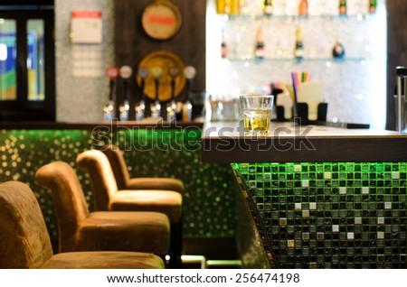 Empty bar with a tumbler of whiskey on the counter in front of a row of empty seats with the beer taps and bottles on shelves in the background - stock photo
