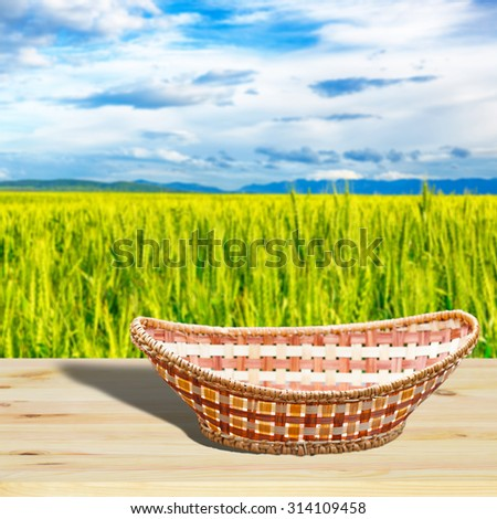 Empty basket on wooden table.Blurred wheat field in the background