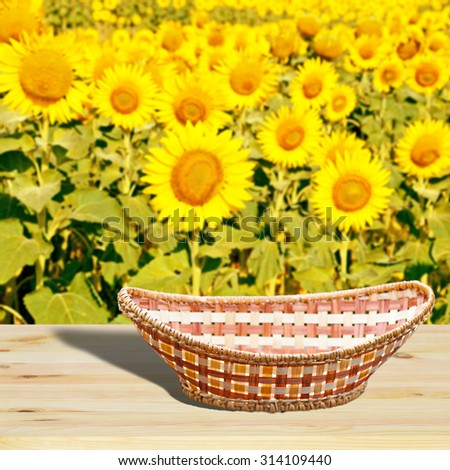 Empty basket on wooden table.In the background blurred field of sunflowers - stock photo