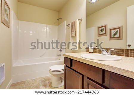 Empty bathroom interior in soft ivory color. Bathroom vanity cabinet with large mirror and beige tile floor