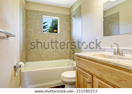 Empty bathroom with tile wall trim, small window and wooden vanity cabinet with mirror