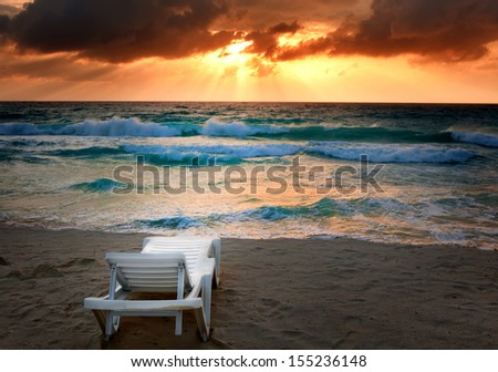 Empty beach chair before sea, sunset