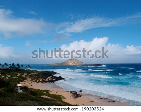 Empty beach due to large wave and view of islands on a cloud filled day at Makapuu Beach Park, Oahu, Hawaii.                               - stock photo