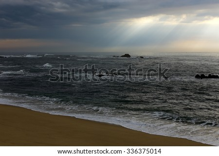Empty beach in a cloudy spring sunset with sunbeams - stock photo