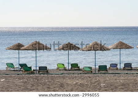 empty beach with sun shades and beach chairs - stock photo