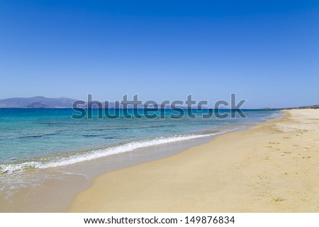 empty beach with turquoise ocean and an island in background. - stock photo