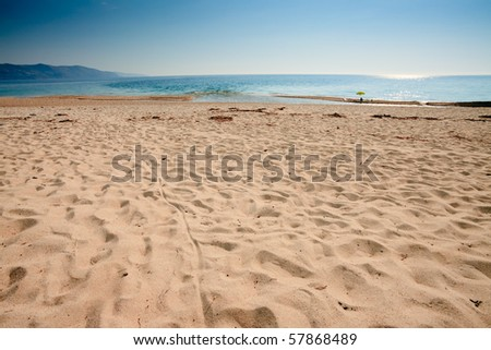 Empty beach with yellow umbrella, Corsica, France - stock photo
