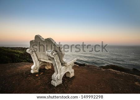 Empty bench at beach - stock photo