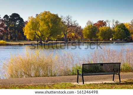 Empty bench by lake with Fall trees - Washington Park - Denver, Colorado - stock photo
