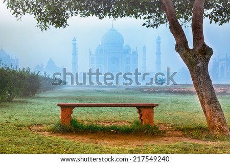 Empty bench by Taj Mahal hidden in morning fog - stock photo