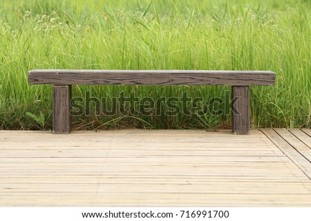 empty bench in a park on wooden planks and long green grasses in the back
