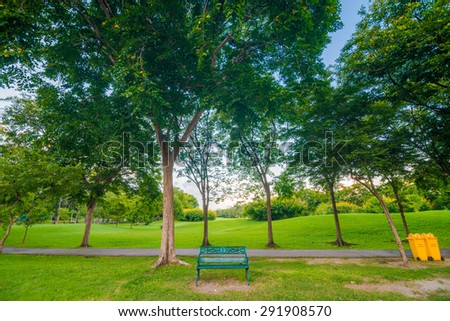 Empty bench in green park and sky with sun light, Green park outdoor - stock photo