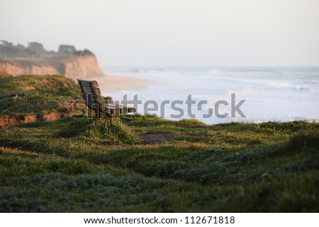 Empty bench on cliff overlooking half moon bay at sunset - stock photo