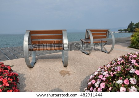 Empty benches on lakeshore of Garda lake, Bardolino, Italy