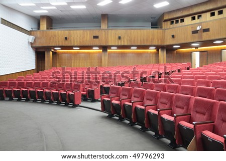 Empty big yellow conference room with red armchairs - stock photo