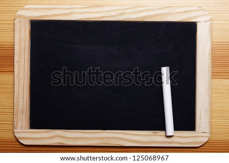 Empty Black board with wooden frame and a piece of chalk.