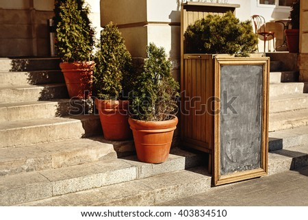 empty black chalk board in classical frame for advertising or menu, space for text in city street - stock photo