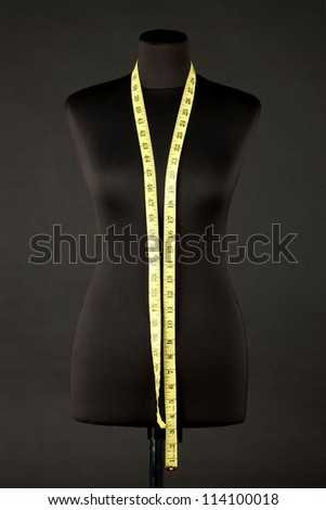 empty black mannequin with measuring tape isolated on black - stock photo