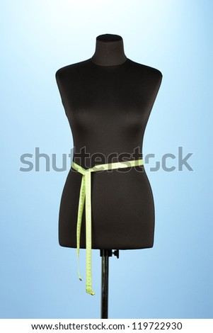 empty black mannequin with measuring tape  on blue background - stock photo