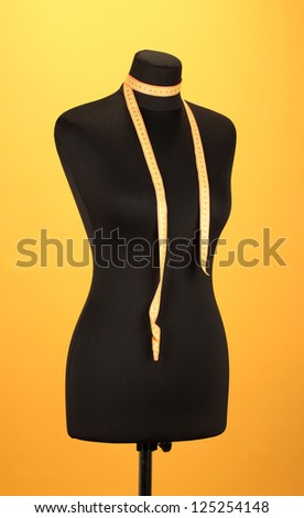 empty black mannequin with measuring tape  on orange background - stock photo