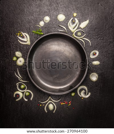 empty black plate with frame of onion slices and spices on dark stone background, top view, copy space - stock photo