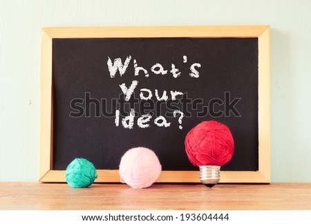 empty blackboard and bulb idea concept made from wool balls over wooden shelf - stock photo