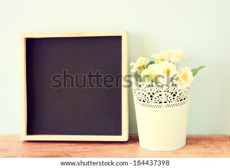 empty blackboard and flowerpot over wooden shelf, retro filter - stock photo