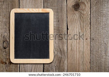 Empty blackboard on old wooden background - stock photo