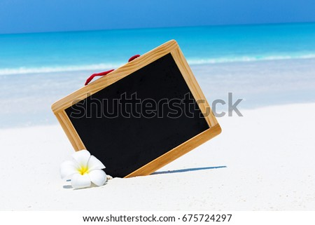 Empty blackboard on sandy beach decorated white plumeria flowers, concept travel and aroma spa card with free space for your text