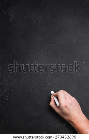 empty blackboard with a hand starting to write